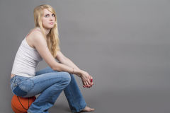 Sporty Caucasian Blond Female Sitting on Basketball Ball in Stud Royalty Free Stock Photo