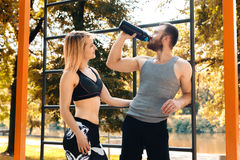 Sporty caucasian couple is resting after workout training in a p Royalty Free Stock Photo