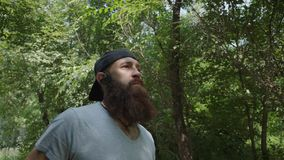 Sporty caucasian man in headphones jogging in the green park. Outdoors. Portrait shot. A brutal man with a beard runs in the forest. He looks ahead. Concept stock footage