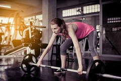 Sporty caucasian woman exercise with barbell,Female does the exercising at gym royalty free stock photography