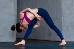 Sporty Caucasian woman practicing standing side angle twist position during yoga class.  Stock Image