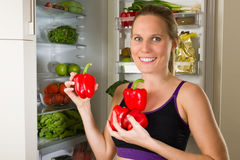 Sporty, Caucasian woman showing vegetables for healthy eating Stock Image