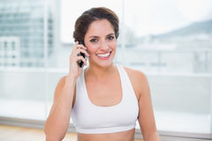 Sporty cheerful brunette phoning Royalty Free Stock Photography