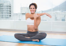 Sporty cheerful brunette stretching on exercise mat Stock Photography