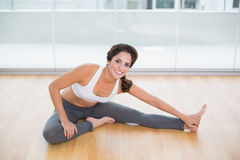 Sporty cheerful brunette stretching on the floor Royalty Free Stock Images