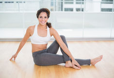 Sporty cheerful smiling brunette stretching on the floor Royalty Free Stock Image