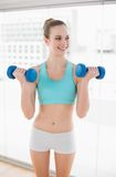 Sporty cheerful woman holding dumbbells and looking away Stock Photography