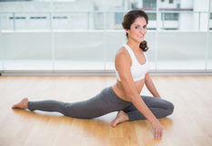 Sporty cheery brunette stretching on the floor Royalty Free Stock Photos