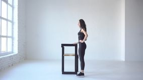 Sporty chuderlawy żeński trener robi kopnięciom podczas gdy opierający na krześle w białym odosobnionym studiu Boczny długi widok zdjęcie wideo