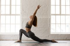 Sporty woman practicing yoga, standing in anjaneyasana pose, Horse rider. Sporty concentrated woman in grey sportswear, bra and leggings practicing yoga stock photography