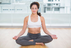 Sporty content brunette sitting in lotus pose with eyes closed Stock Photography