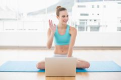 Sporty content woman sitting cross-legged in front of laptop waving Stock Photo