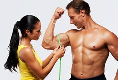 Sporty couple. Woman measuring athletic's men biceps Stock Images