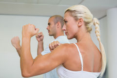 Sporty couple clenching fists at fitness studio Stock Photography