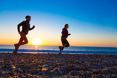 Sporty Couple doing Morning Jogging on Sea Beach at Sunrise Stock Images