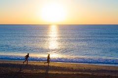 Sporty Couple doing Morning Jogging on Sea Beach at Sunrise Stock Photo