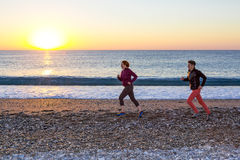 Sporty Couple doing Morning Jogging on Sea Beach at Sunrise Stock Photography