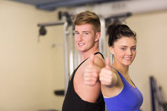 Sporty couple gesturing thumbs up in the gym Royalty Free Stock Image