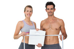 Sporty couple holding scales and measuring tape Royalty Free Stock Photo