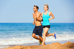 Sporty couple jogging together on the beach Stock Image