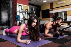 Sporty couple makes plank exercices. Sporty young couple makes plank exercices in the gym royalty free stock photos