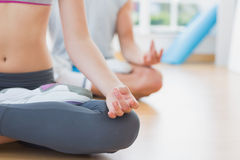 Sporty couple in meditation pose at fitness studio Royalty Free Stock Photo