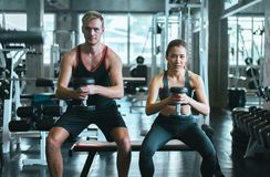 Sporty couple man and woman exercise with dumbbells or does the exercises at gym royalty free stock image