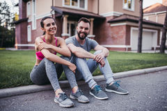 Sporty couple outdoors. Sporty couple is sitting on border and having rest from running outdoors near modern private houses. Smiling and looking at camera royalty free stock images