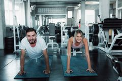 Sporty Couple are Push-Up Exercising in Fitness Gym., Portrait of Young Pretty Woman is Working Out Against on Sport Bodybuilding. Equipment Background royalty free stock photo