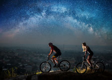Sporty couple riding a bicycles at night under starry sky. Sporty friends riding a bicycles on the mountain hill at night under starry sky and Milky way. Below Royalty Free Stock Photos