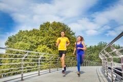 Sporty couple running across a bridge in summer Stock Photo