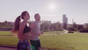 Man and woman running in city park stock footage