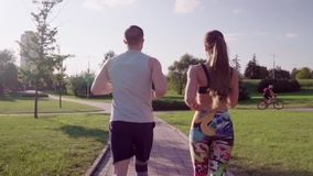 Man and woman running in city park stock video