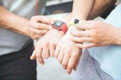 Sporty couple sharing workout data from their smartwatches. Stock Photography