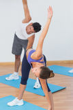Sporty couple stretching hands at yoga class Stock Images