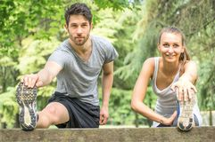 Sporty couple stretching legs outdoors. Couple stretching legs after run outdoors- Young athletes getting warm for a run in the park Stock Images