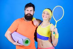 Sporty couple training with fitness mat and tennis racket. Sport equipment. Athletic Success. Happy woman and bearded stock photography