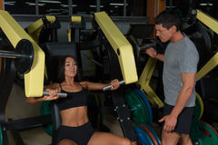 Sporty couple trains on exercise machine in gym. Active lifestyle, men and women in fitness club Royalty Free Stock Image