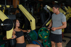 Sporty couple trains on exercise machine in gym stock photography