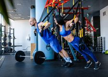 Sporty couple workout in the gym, doing exercise with functional loops. royalty free stock images