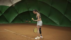 Sporty disable girl taking a ball from a basket, walk to the middle and make a strong shot with the tennis racket. Indoors stock footage