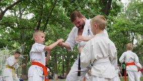 Sporty dla dzieciaków, trener wydają instrukcj batalistyczne chłopiec w kimonie, sztuki samoobrony trenuje w parku, karate outdoo zbiory