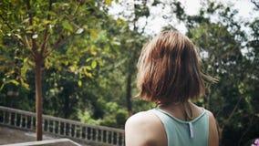 Sporty dziewczyna chodzi w parku z kwiatami zbiory wideo