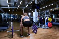 Sporty dziewczyna robi ćwiczeniom w gym z barbell zdjęcie stock