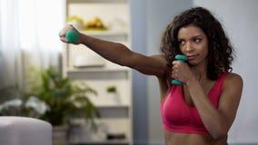 Sporty dziewczyna robi bokserskich ruchy z dumbbells w rękach, sprawność fizyczna trening zdjęcia royalty free
