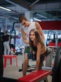 Sporty dziewczyny szkolenie z dumbbells na kolorowym gym tle Trener pomaga jej klienta w sprawność fizyczna klubie Zdjęcie Stock