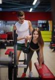 Sporty dziewczyny szkolenie z dumbbells na kolorowym gym tle Trener pomaga jej klienta w sprawność fizyczna klubie Zdjęcia Stock