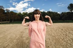 Sporty energetic athletic woman wears pink sports top smiles as shows her biceps, likes sport and active lifestyle. People, health and physical activity stock photos
