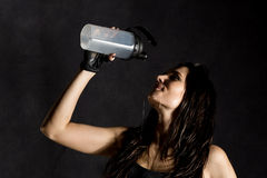 Sporty female boxer or mma fighter drinking and splashing water in her face. beautiful female fitness woman on black Stock Images