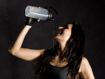 Sporty female boxer or mma fighter drinking and splashing water in her face. beautiful female fitness woman on black Stock Photos